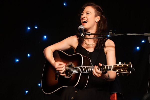 Jenn Butterworth laughing on stage with her Martin D41 guitar