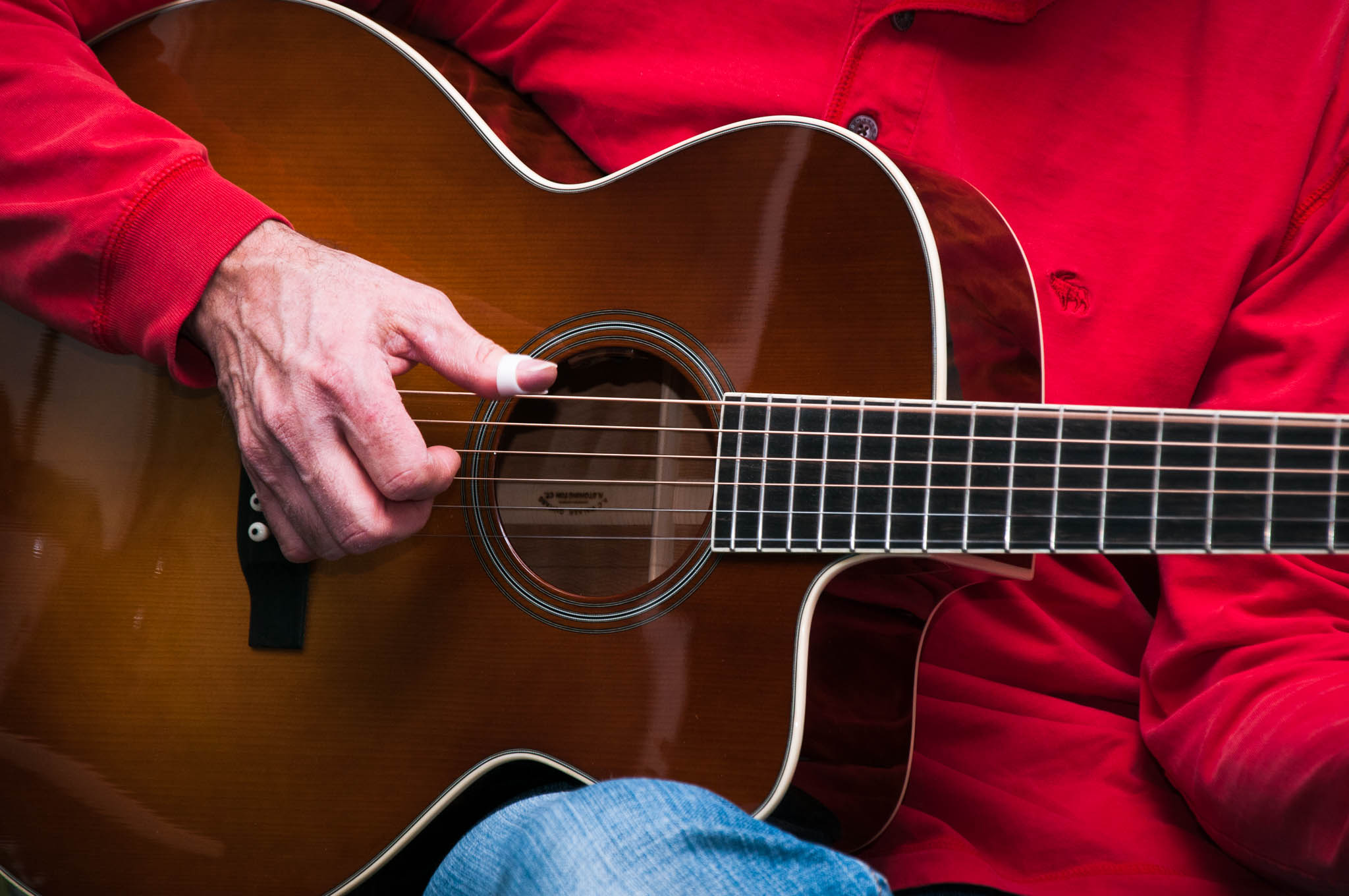 Close-up of a man playing an acoustic guitar with a cutaway and a sunburst top.