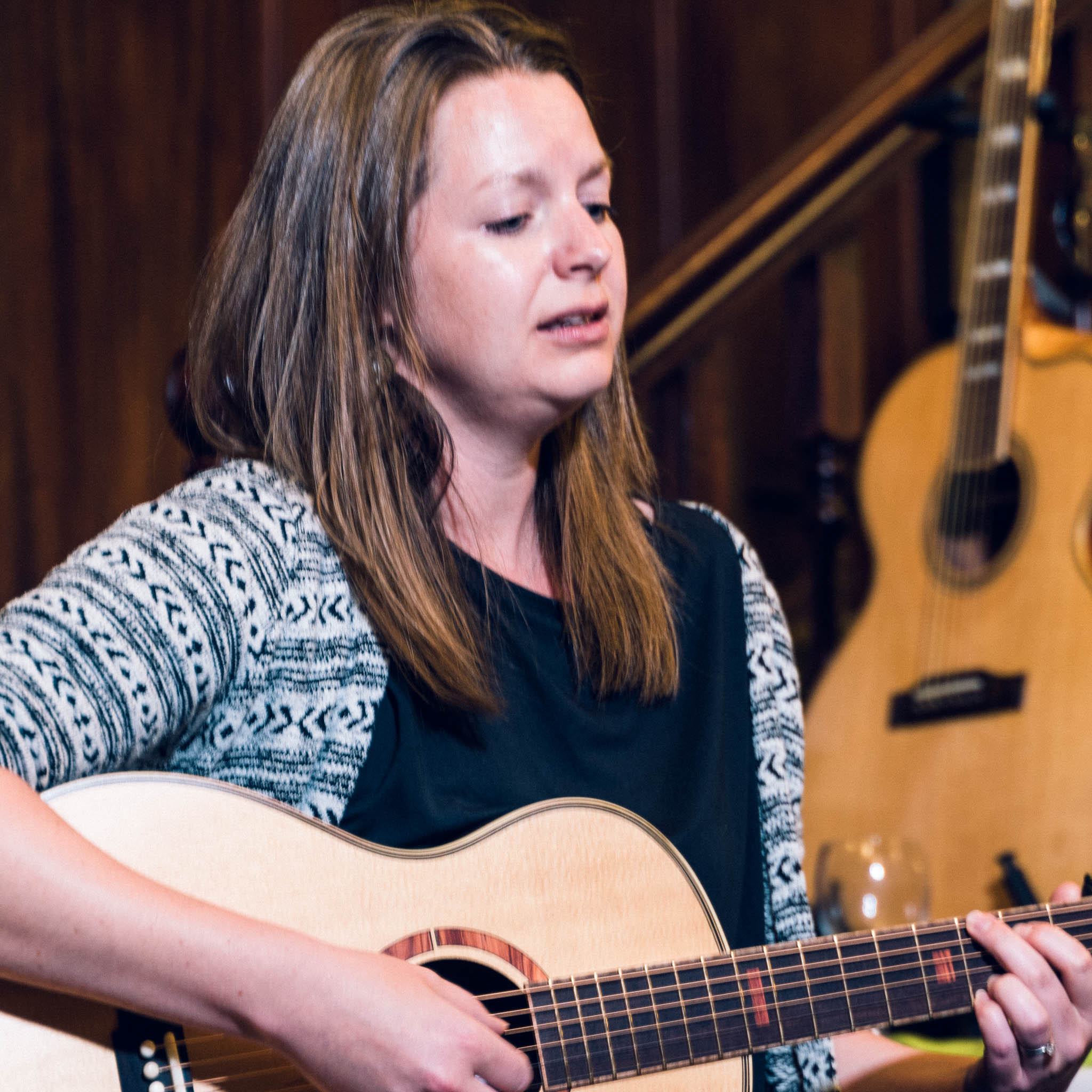 Square crop of Rosie Heydenrych playing acoustic guitar and singing